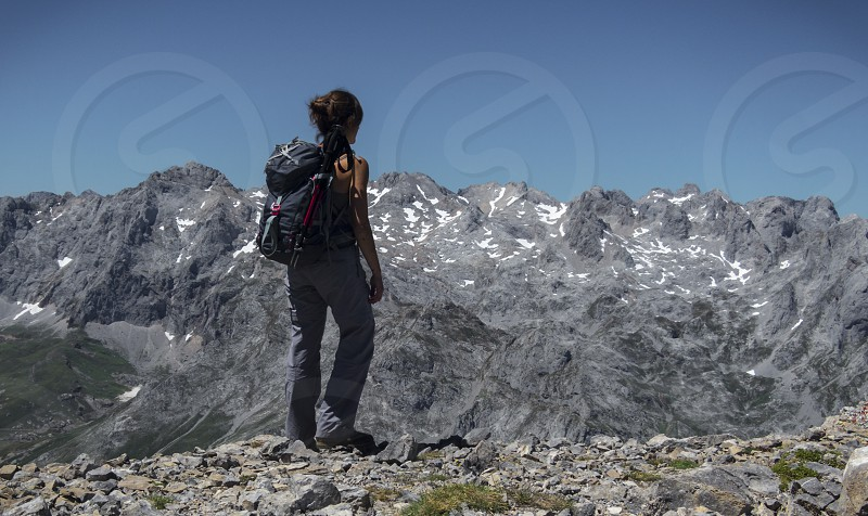 WOMAN WALKING IN PICOS DE EUROPA MOUNTAINS. ASTURIAS. SPAIN. Enjoying nature and freedom in the countryside. Walking around mountain in summer. Life peace happiness are some of the sensations and emotions  that you can feel breathing deep while you get up a hill listening to the world and inside of you. Alone or sharing these moments. Silence if the day is quite. Being and knowing yourself when the condictions are extreme. Let´s take care for it. photo