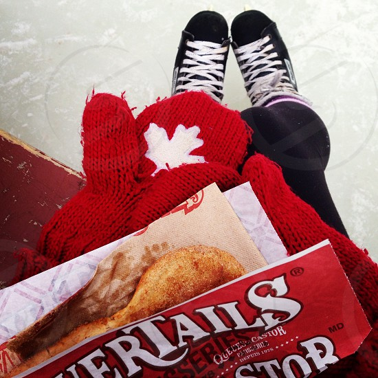 Skating in the winter on the Rideau Canal in Ottawa Canada with Canadian mittens and a Beavertail pastry. photo
