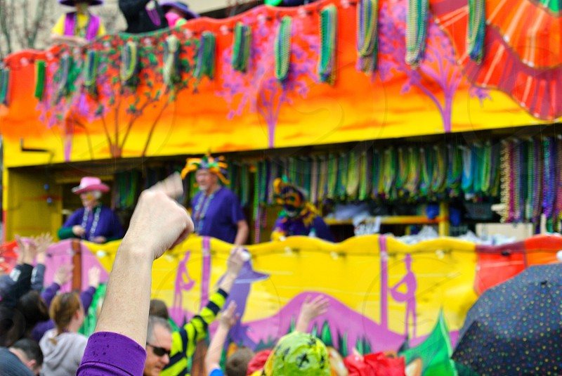 Mardi Gras float in a parade in Lafayette Louisiana (Cajun Country) w/ people reaching their hands out to catch beads photo