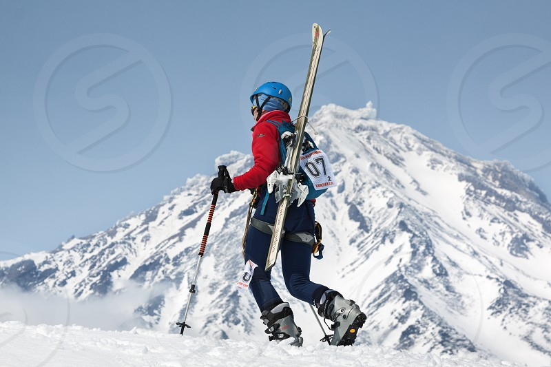 AVACHA VOLCANO KAMCHATKA RUSSIA - APR 21 2012: Open Cup of Russia on ski-mountaineering. Girl ski mountaineer climbing on mountain with skis strapped to backpack on background active Koryak Volcano. photo