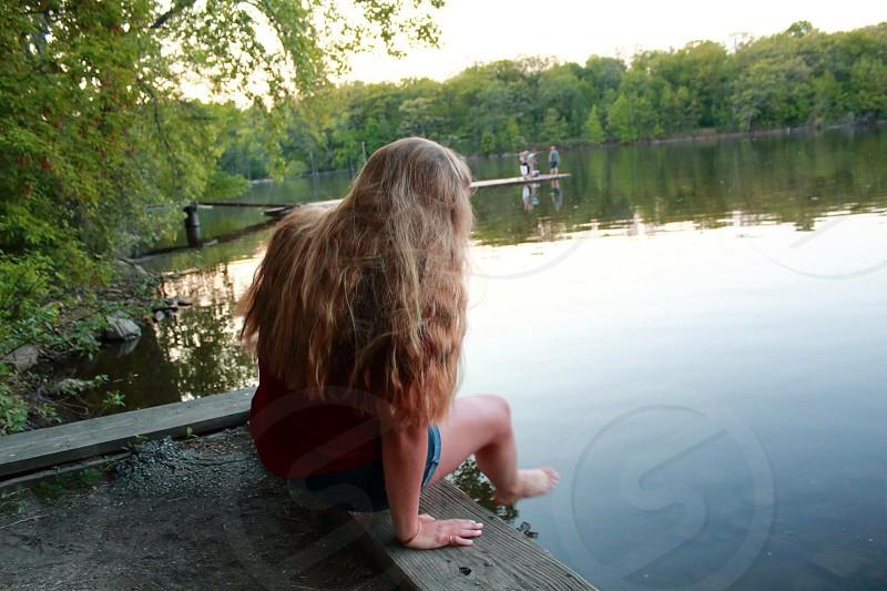 woman wearing blue shorts sitting near body of water photo
