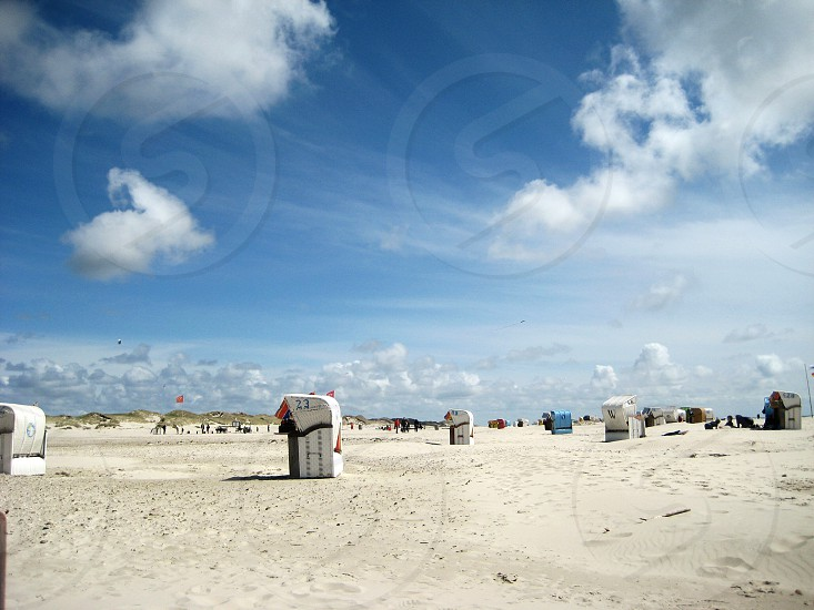 white sand with white blue and brown stalls under white clouds and blue sky photo