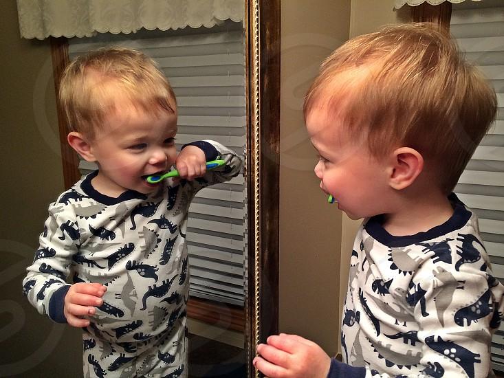 Child brushing teeth in mirror photo