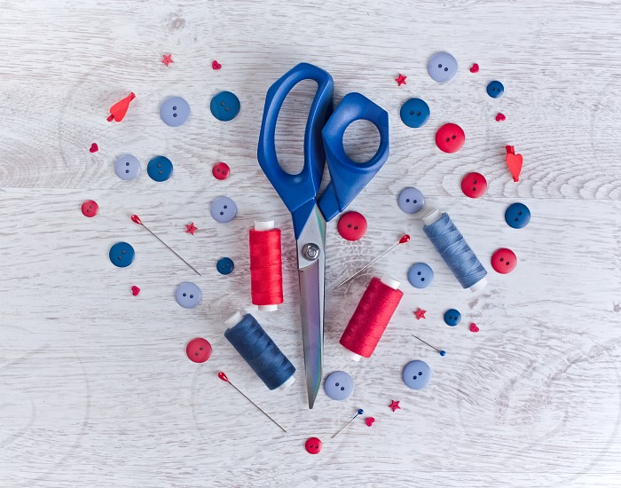 Scissors threads pins and buttons on wooden white table photo