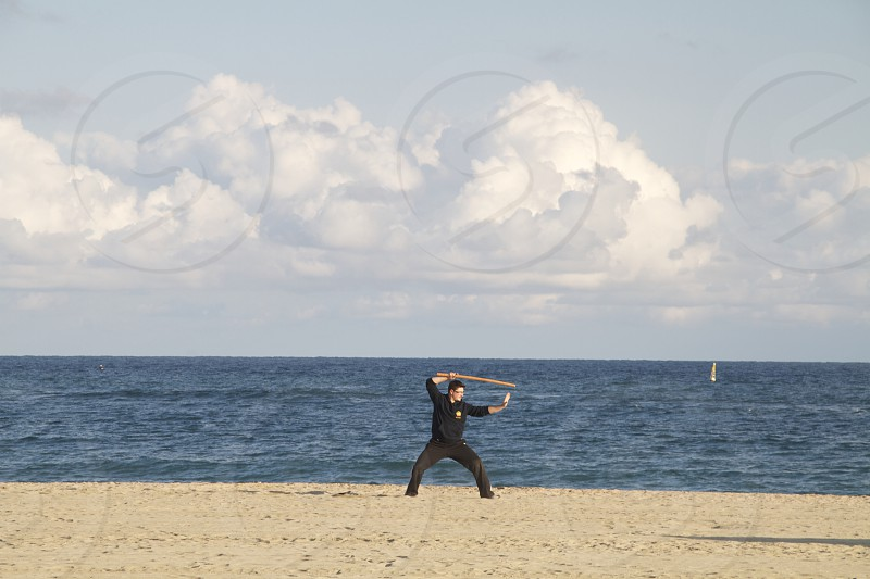 man holding a wooden sword at the beach with cloudy sky photo