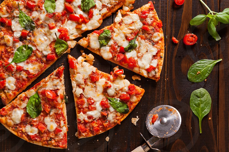 Overhead view of a margherita pizza on a dark wooden surface with ingredients and pizza cutter photo