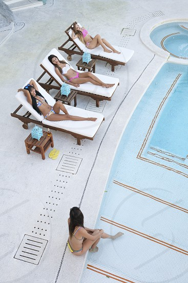 Four young women tanning and enjoying day at swimming pool photo