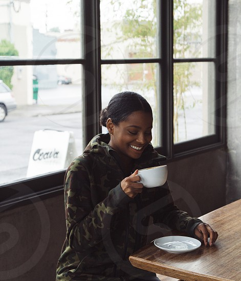smiling woman wearing black green and maroon camouflage hoodie holding white ceramic cup photo