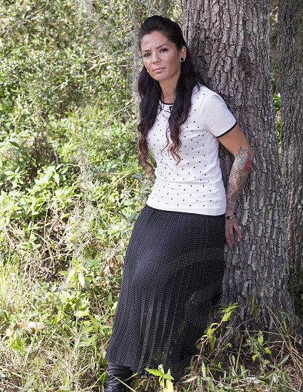 well dressed woman standing near tree in the woods photo