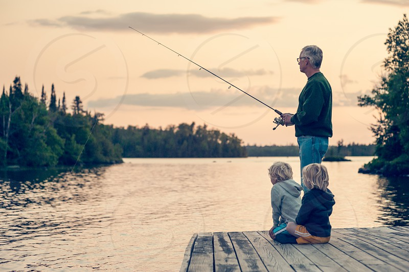 grandpa grandchildren grandson kids youth old young age life learning teaching fishing fish lake wonder trees forest male boys man sweatshirt sunset pole rod reel glasses reflection sky clouds dusk dock yellow blue watching waiting patience photo