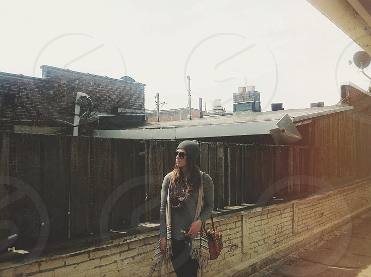 woman in grey shirt and beanie in sunglasses near wooden fence photo
