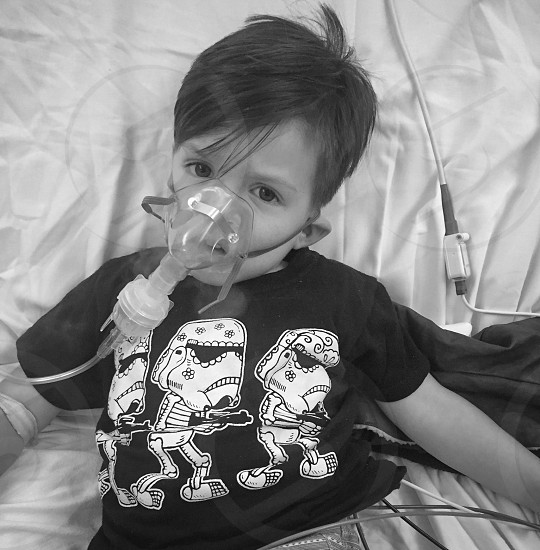 grayscale photo of child wearing mask nebulizer while lying on bed photo