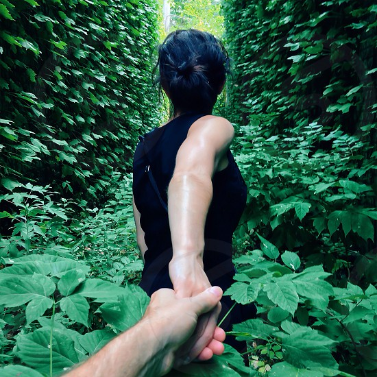 woman in black sleeveless shirt leading man through greenery photo