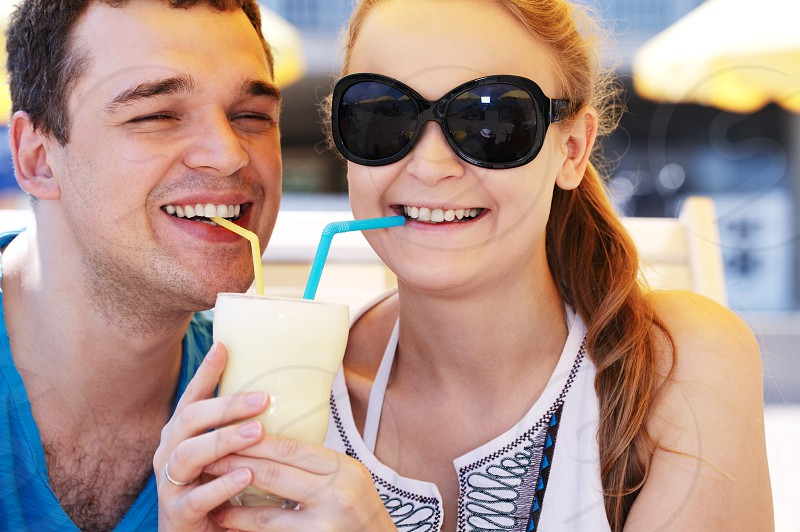 Romantic young couple sharing a cocktail each drinking from their own straw as they enjoy their tropical summer vacation photo