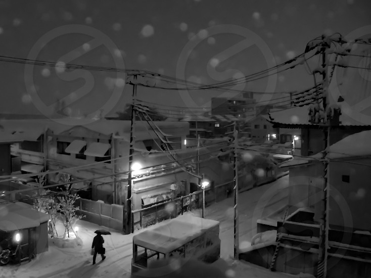 grayscale photo of person with umbrella walking on street during a snowy night photo