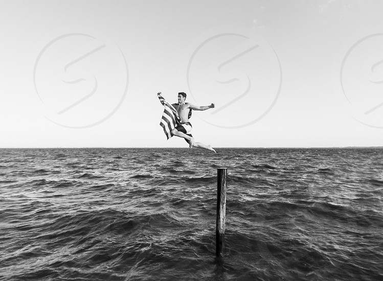 man jumping into water grayscale photography photo