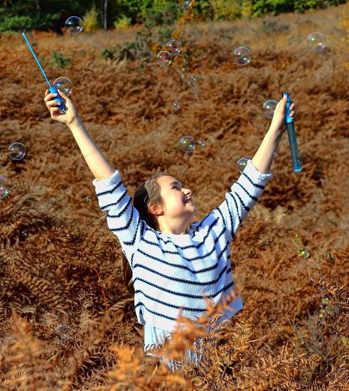 bubbles girl joy young blowing bubble wand ferns winter sun autumn spring blow  photo