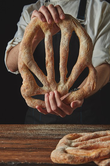 Organic fresh fougas bread in the hands man on a black background photo