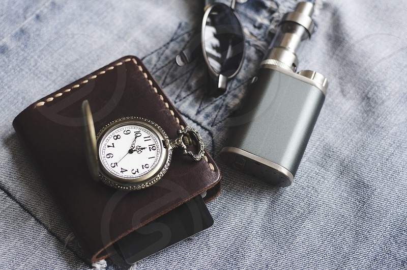 Man accessories watch wallet e cigarette and glasses on blue jeans photo