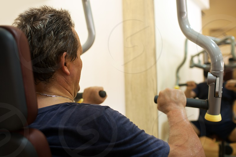 Mature man having a workout on shoulder press machine his reflection in the mirror. Active and healthy lifestyle photo