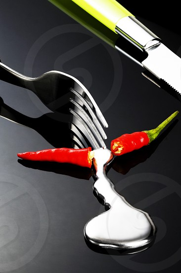 red chili pepper melting a fork while be cutted on a black stone photo