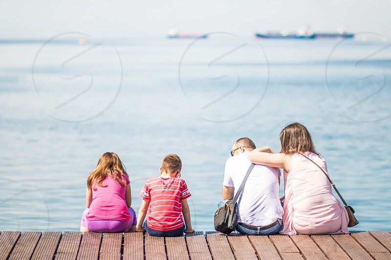 girl in pink shirt purple shorts beside boy in red and white shirt black shorts with man in white shirt grey crossbody bag beside woman in pink sleeveless dress with crossbody bag sitting on photo