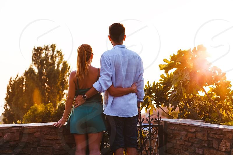 Young couple enjoying sunset on their travel photo