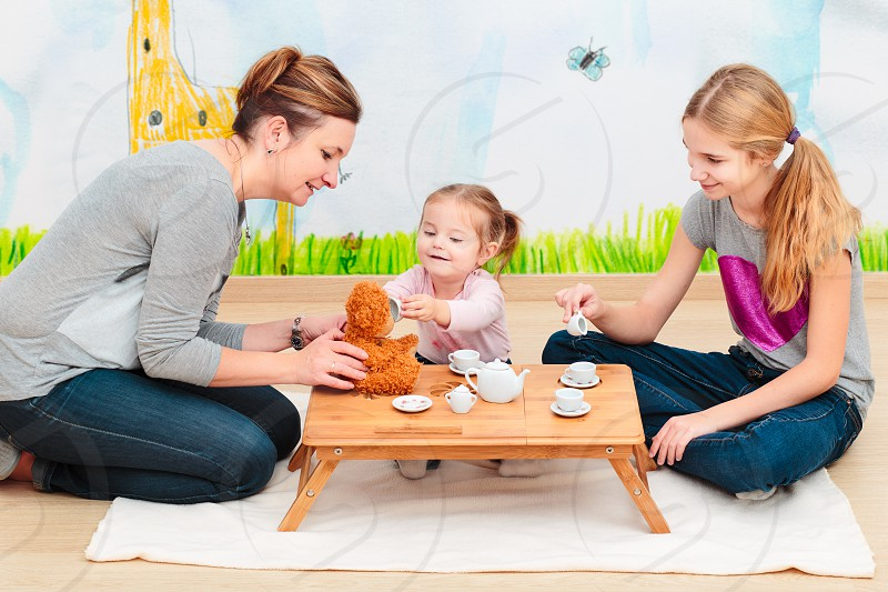 Little girl playing with mom and sister at tea party using childs tea set photo