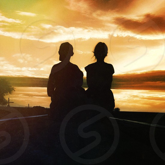 2 person sitting looking on sunrise photo