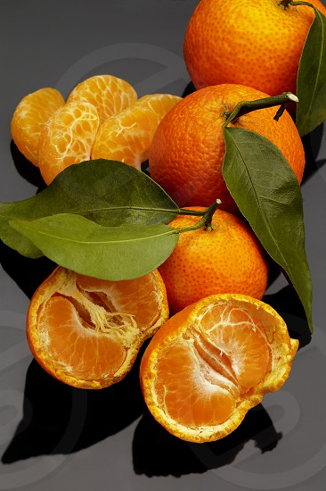 vivid orange tangerine on black reflective surface photo