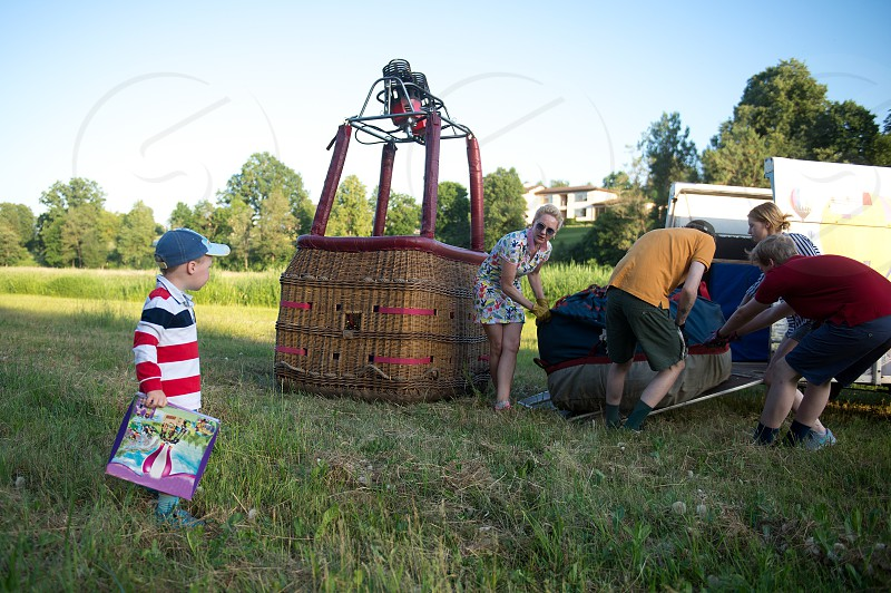 The woman who is the pilot of the hot air balloonmother with her children is preparing the hot air balloon for the flight in the beautiful sunset skies. The journey in the hot air balloon is an unforgettable experience which requires courage bravery and spirit. photo