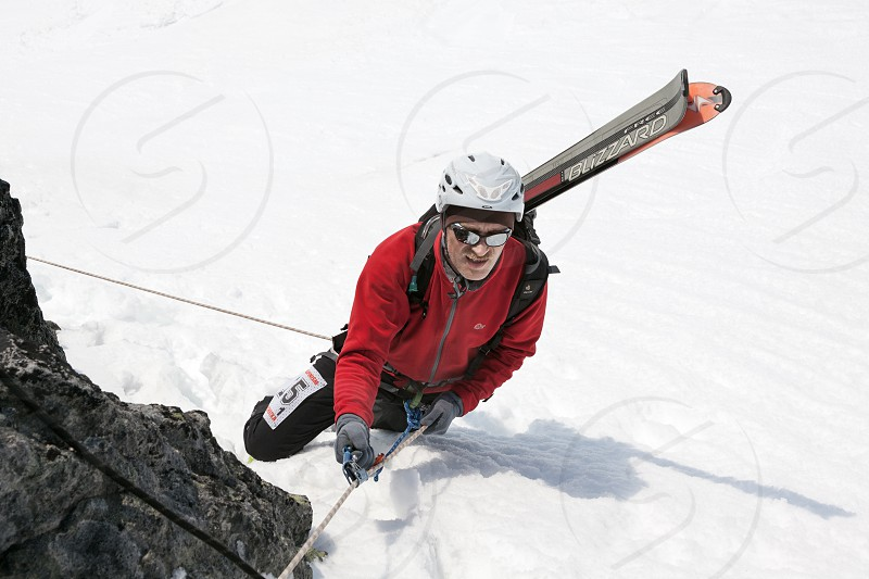 AVACHA VOLCANO KAMCHATKA PENINSULA RUSSIA - APR 21 2012: Open Cup of Russia on Ski Mountaineering on Kamchatka - ski mountaineer climbing on rope on rocky mountain with skis strapped to backpack. photo