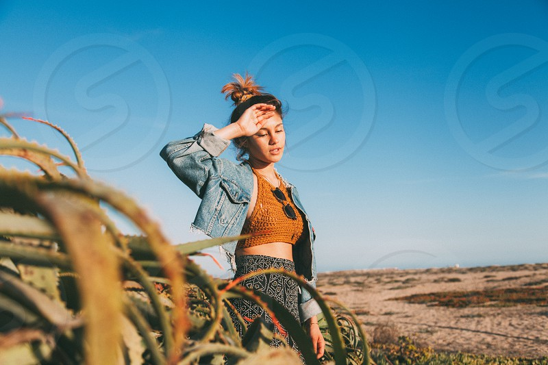 woman in blue denim jacket wiping sweat on her forehead using right hand photo