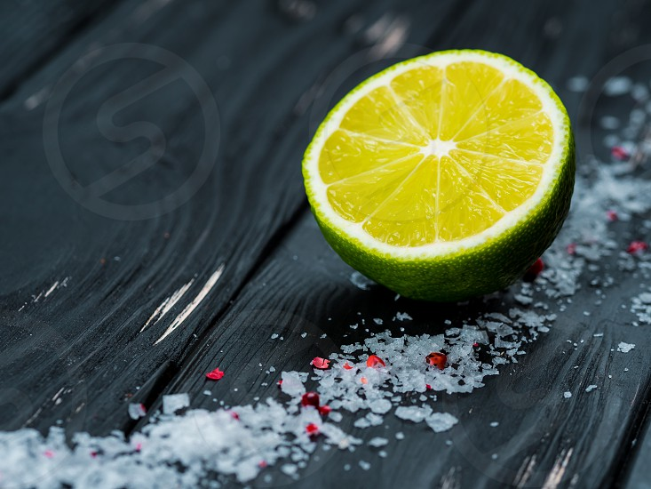 Fresh ripe sliced green lime or lemon and marine salt on black shabby vintage wooden table. Great appetizer for tequila photo