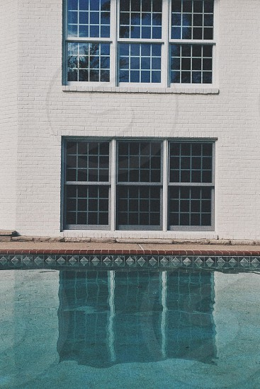 white wooden framed multi-pane window and body of water photo during daytime photo