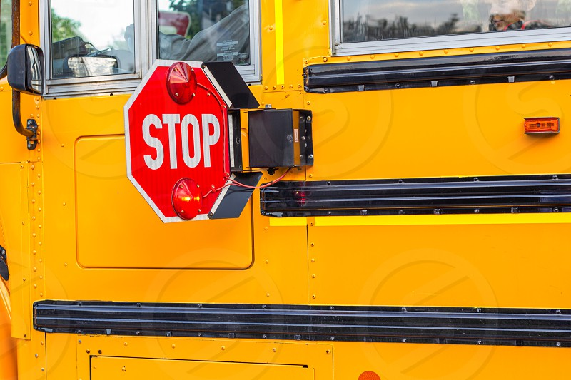 A stop sign with flashing lights is extended from the side of a school bus as it picks up kids requiring drivers to wait until the children are safely aboard. photo
