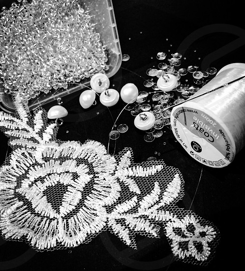 Indoor day black and white monochrome sewing embroidery lace sequins buttons beads thread needle craft tailor tailoring wedding bride dress prepare preparation delicate dainty pretty vintage home made homemade bridal marriage sew make gems stones shiny glass sparkly sparkling pearl net veil photo
