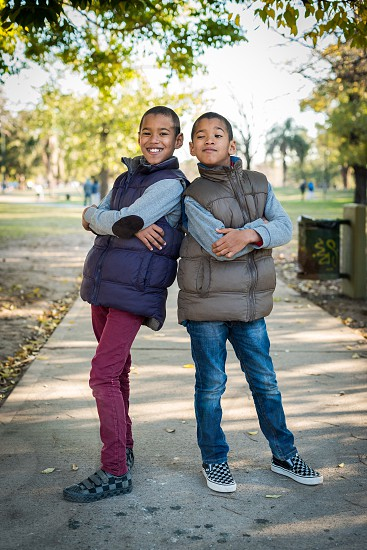 twin kids with light dark skin color having fun and fooling around outside at the park at autumn time posing like for a fashion shoot photo