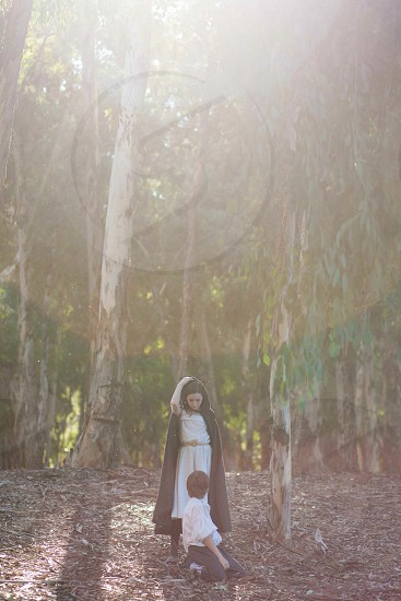 woman wearing a white dress and black cape in a forest photo