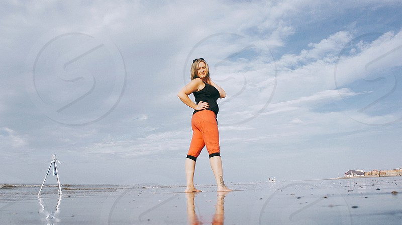 woman wearing black tank top standing on wet surface under white clouds during daytime photo