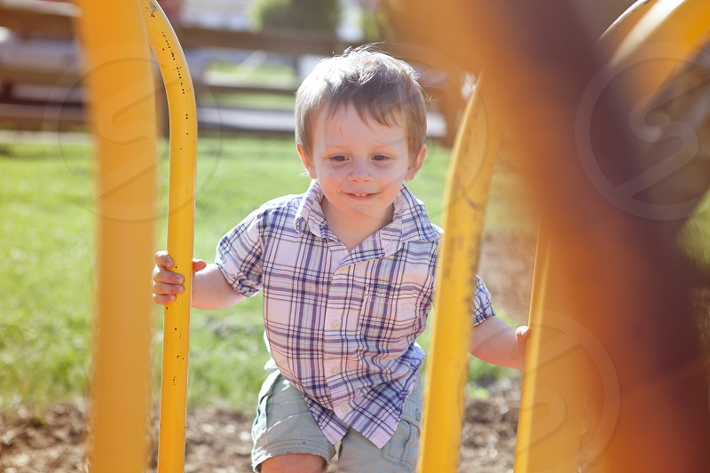 small boy on yellow outdoor toy set photo
