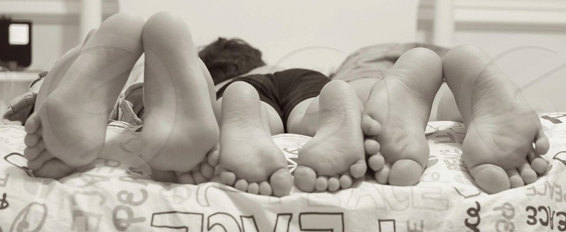 Black and White monochrome of 3 siblings showing the difference in their feet size.  photo