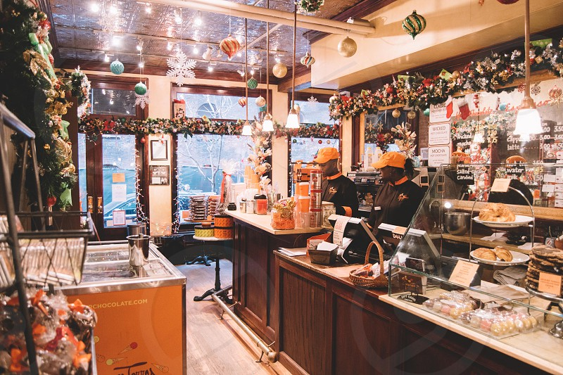 people standing on counter in front of freezer under hanging baubles and buntings inside shop photo