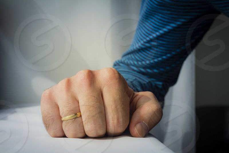 Man with a wedding ring squeezed his hand on white cloth background. photo