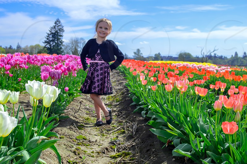 girl on black blazer standing near purple and pink petaled flower field during daytime photo
