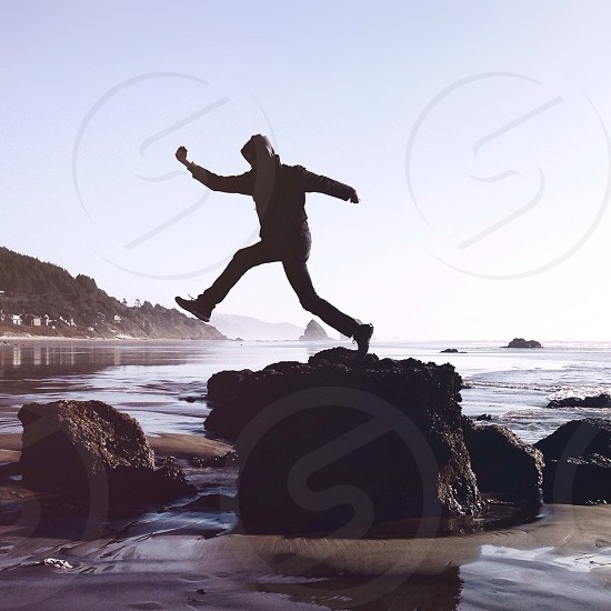 figure wearing black leaping off black rock in  ocean photo