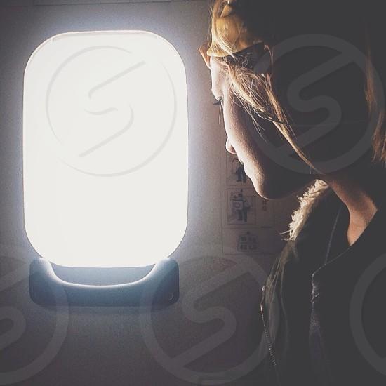 woman wearing black jacket near airplane window photo