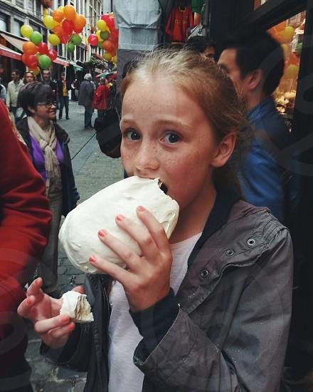 Girl eating giant meringue in Belgium photo