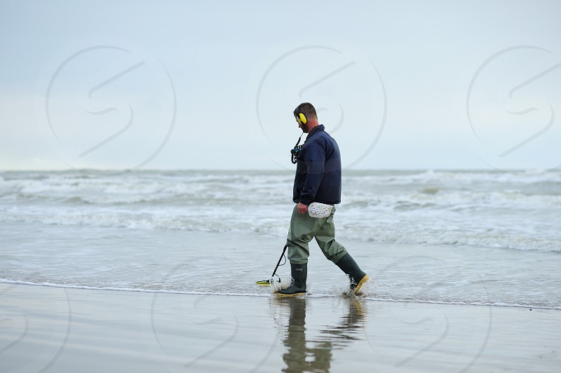 man in black gray and yellow galoshes walking on seaside photo