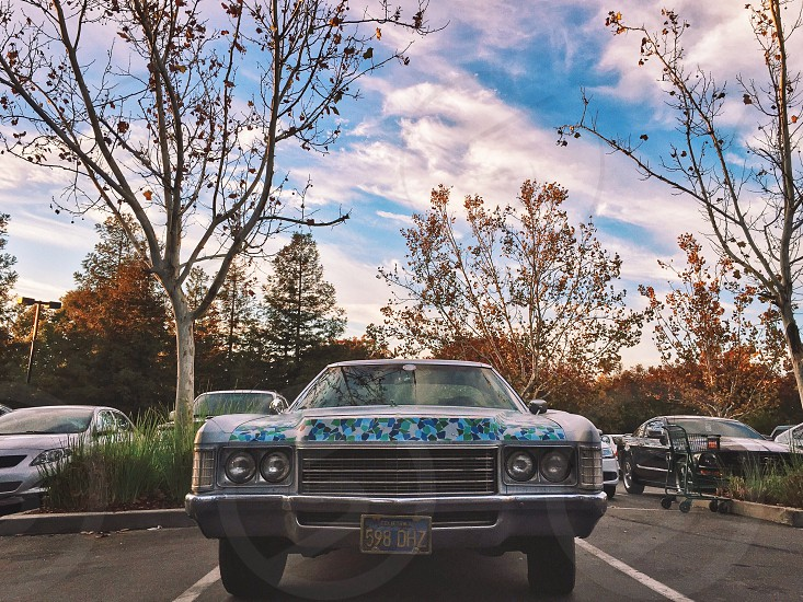 blue green and white speckled vintage car with license plate 598 daz backed into parking spot in parking lot under orange leaf trees photo